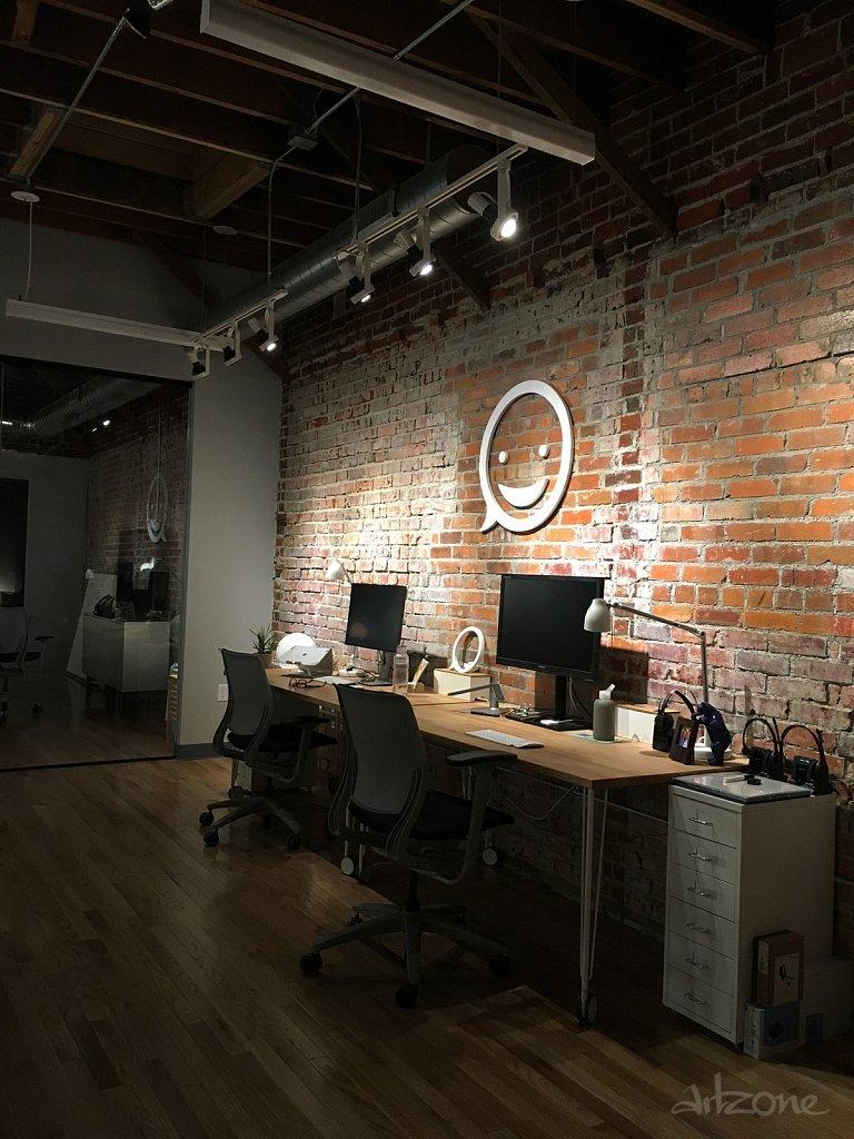 Дървен надпис лого на тухлена стена в офис - индустриален стил