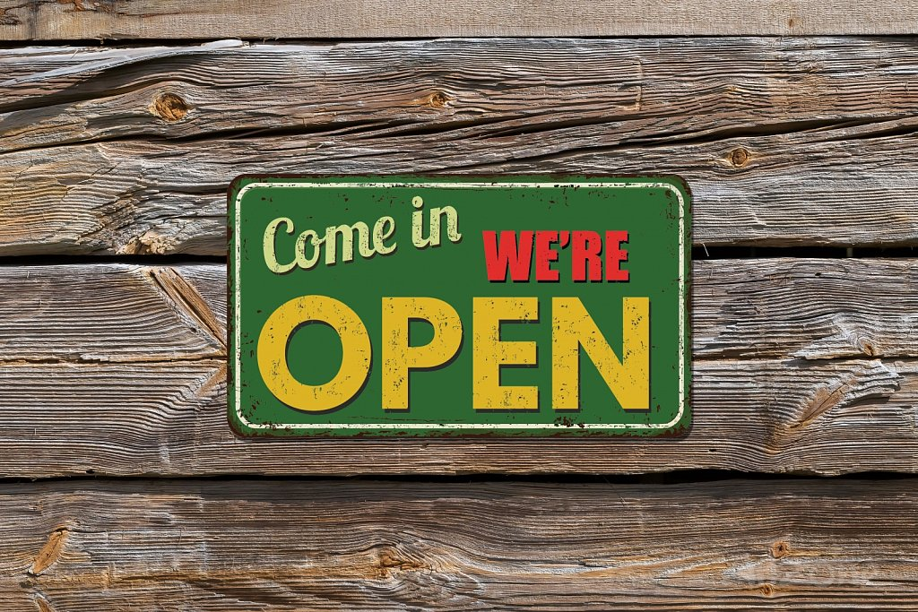 Come in we are OPEN sign in yellow and green